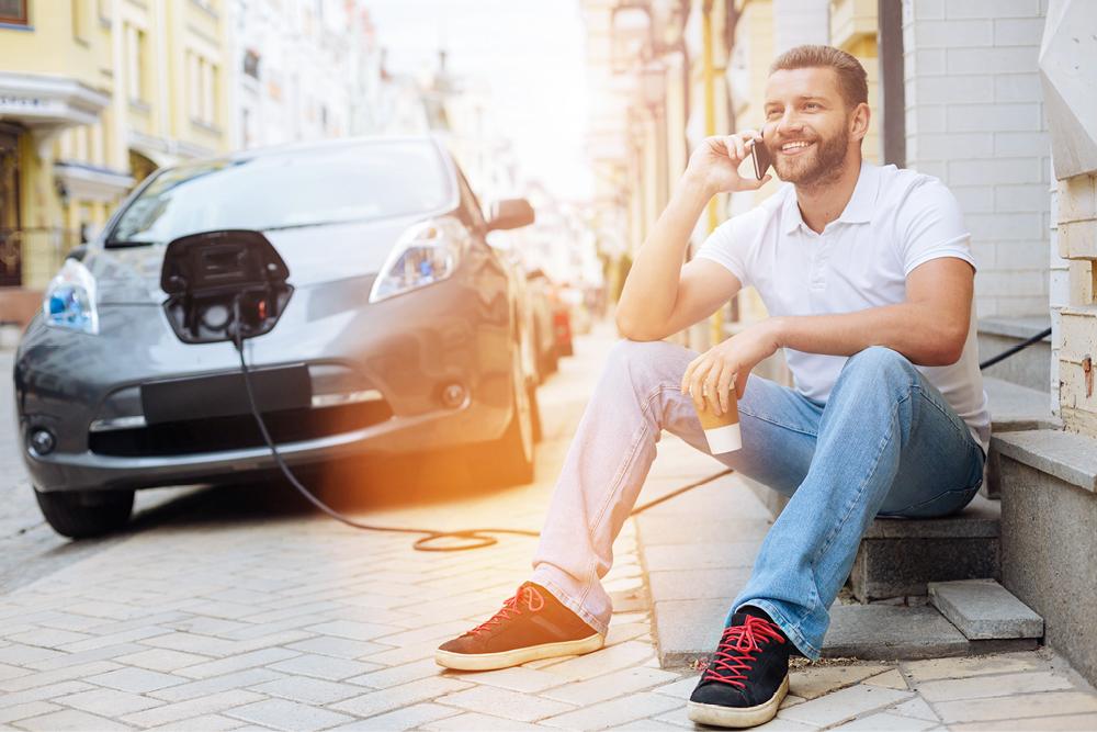 Elektroauto das im Hintergrund geladen wird mit Mann am Handy im Vordergrund.